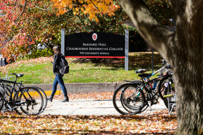 A pedestrian walks past parked bikes and a sign for Barnard Hall and Chadbourne Residential College at the University of Wisconsin-Madison.