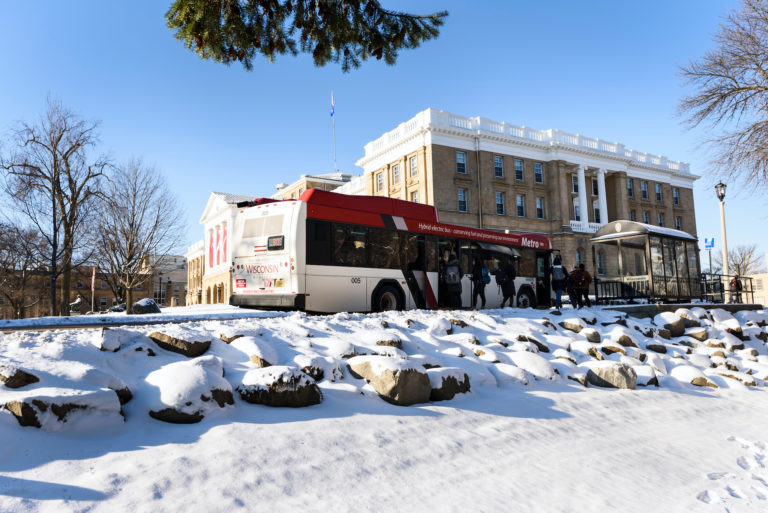 Freshly-fallen snow covers the ground as a Metro city bus makes a stop on Observatory Drive near Bascom Hall at the University of Wisconsin-Madison during winter on March 14, 2017.