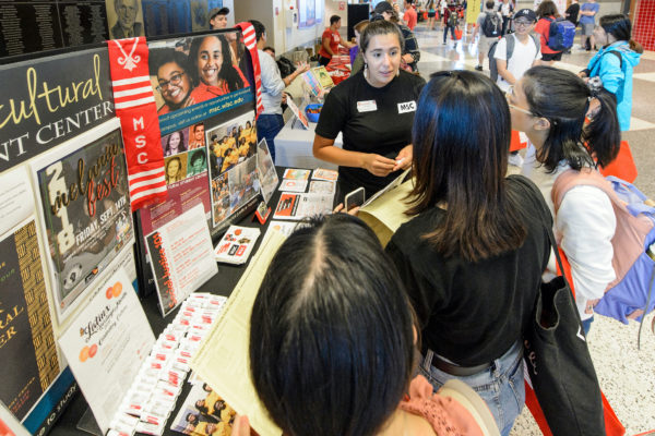 Students check out the Multicultural Student Center booth during the Fall Student Organization Fair at the Kohl Center at the University of Wisconsin-Madison. on Sept. 12, 2018. The two-day fair is an opportunity for students to learn about special-interest groups, activities and services offered by more than 400 represented student organizations on campus. (Photo by Bryce Richter / UW-Madison)